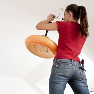 Frau beim Anschließen einer Lampe
