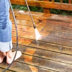Frau reinigt Terrasse mit Hochdruckreiniger