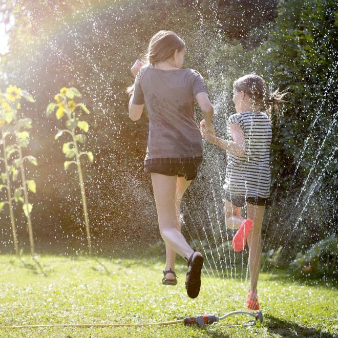Rasensprenger und Kinder im Garten