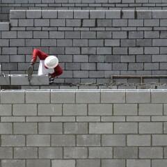 Ein Bauarbeiter zieht eine Wand hoch
