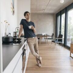 Ein Mann lehnt an einer Küchenzeile, hält einen Becher Kaffee in der Hand und sieht gedankenverloren aus dem Fenster