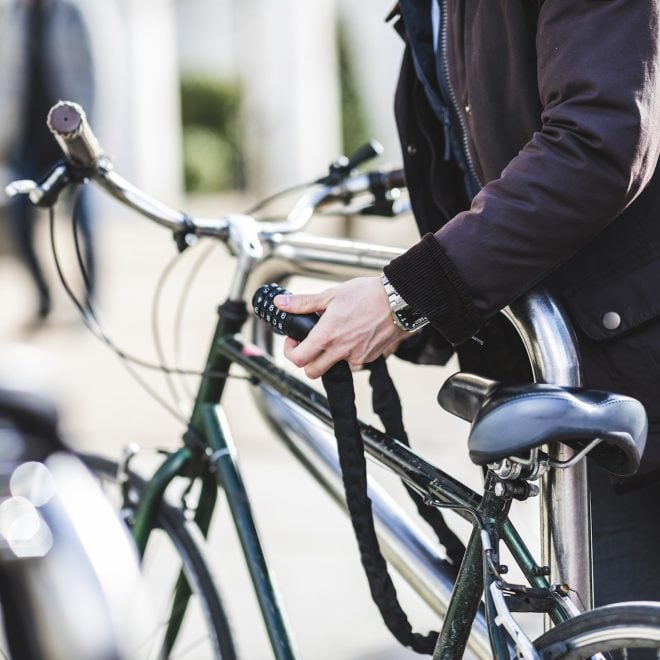Mann schließt Fahrrad mit Fahrradschloss an.