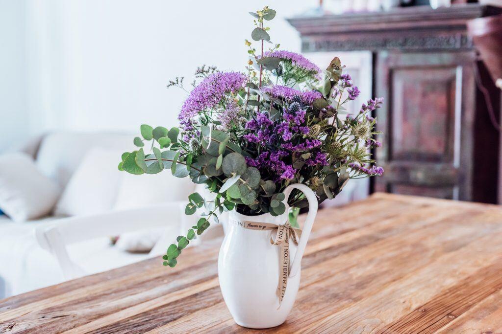 Auf einem Tisch steht eine Vase mit lilafarbenen Blumen und Gräsern