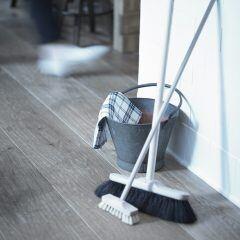 Holzboden mit Putzeimer und Besen zum Reinigen