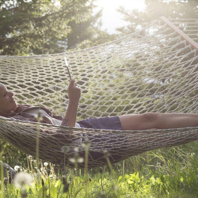 Frau liegt mit ebookreader in der Hängematte in der Natur
