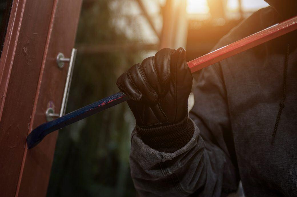 Einbrecher hebelt mit Einbruchseisen eine Fenstertür auf