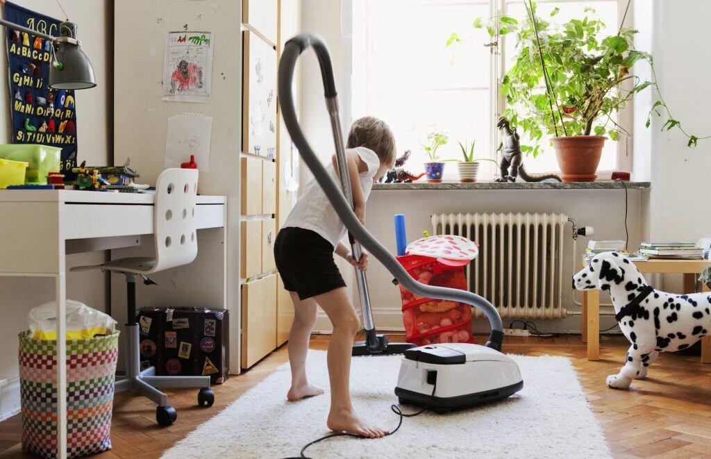 Kind saugt Kinderzimmer