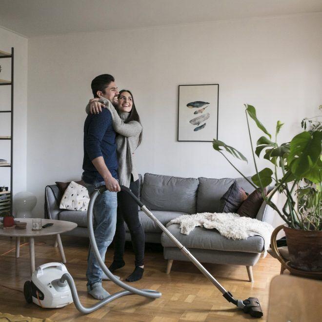 Paar im Wohnzimmer, Mann hält Staubsauger und Frau in der Hand