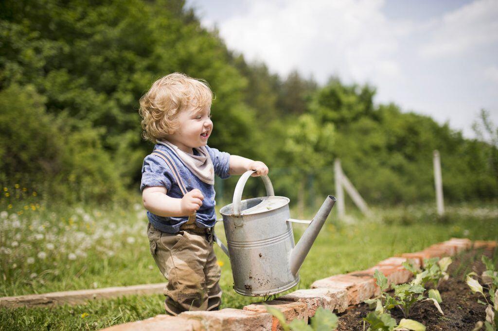 Ein kleiner Junge hält sich an einer Gießkanne fest