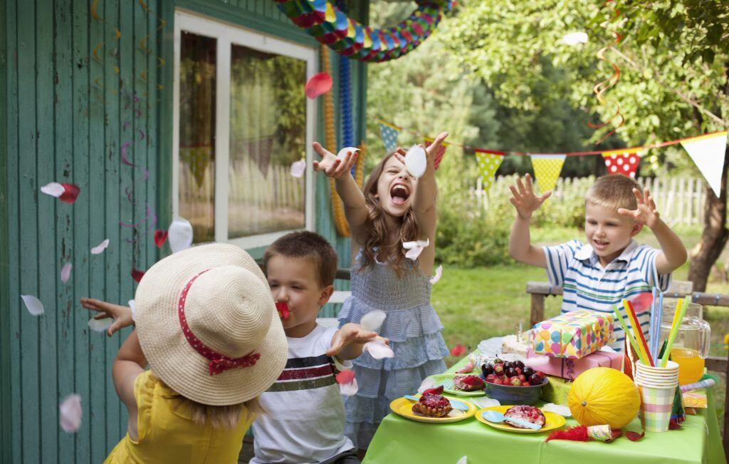 Kinder werfen Konfetti im Garten bei der Geburtstagsparty in die Luft