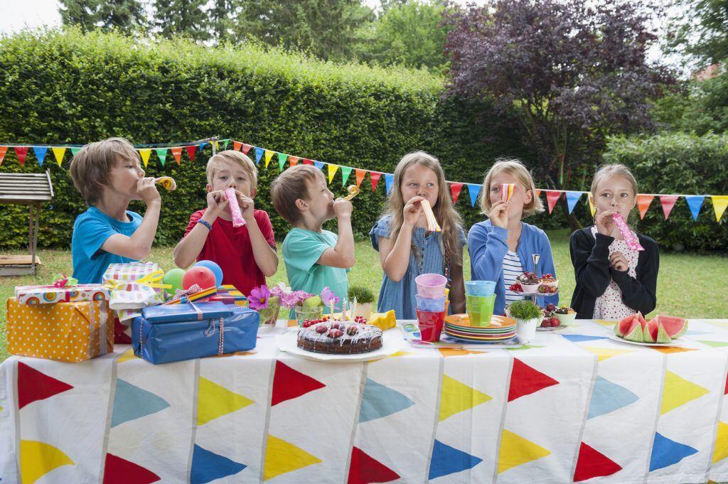 Sechs Kinder stehen an dem Geburtstagstisch und pusten in Luftschlangen