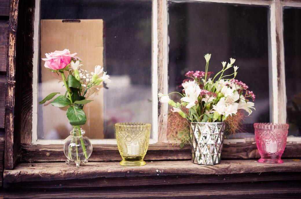 Auf einem Fensterbrett stehen Blumenvasen und Kerzen