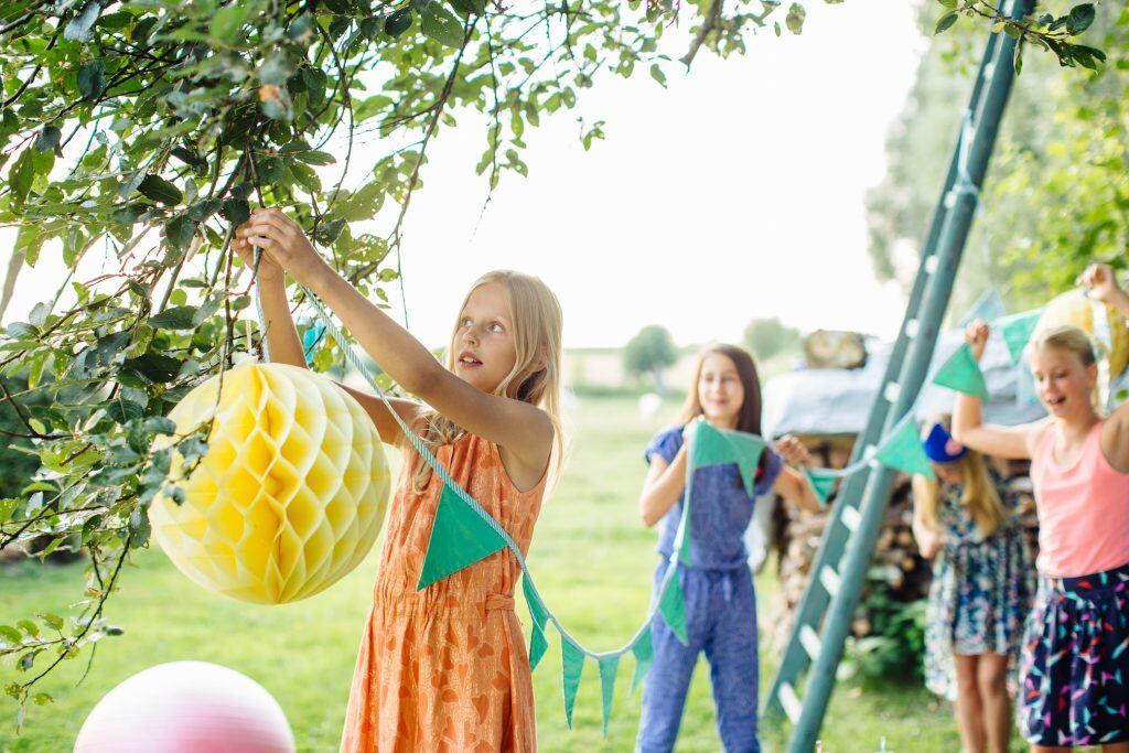 Ein Mädchen hängt Lampions im Garten auf.