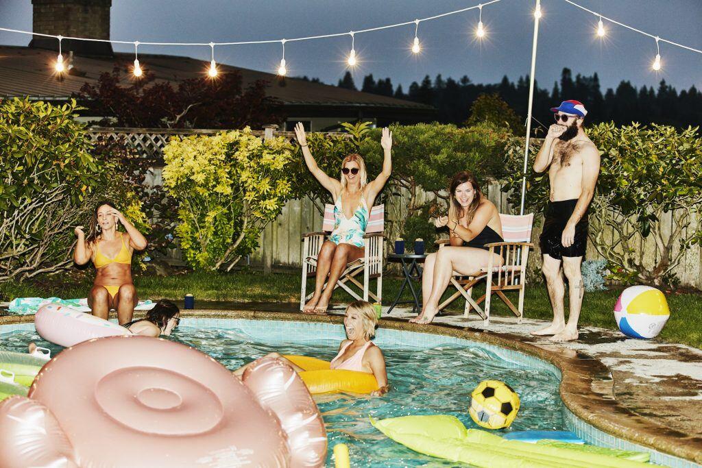 Gäste springen in einen Pool während einer Gartenparty