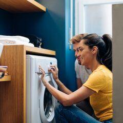 Eine junge Frau und ein junger Mann hocken vor einer Waschmaschine und stellen sie ein.