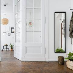 Ein heller Flur mit Garderobe und schmalem Spiegel