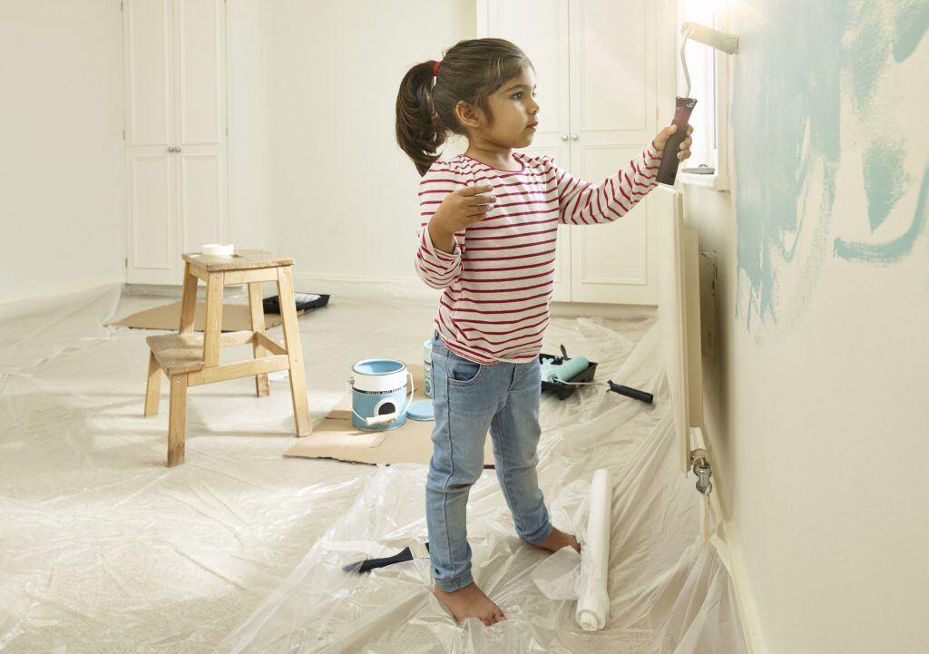 Mädchen malert mit blauer Farbrolle