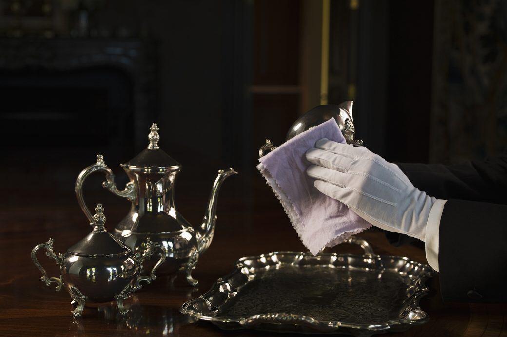 Jemand putzt Silbergefäße mit einem weißen Handtuch und einem weißen Tuch.