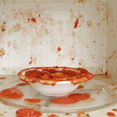Eine Schale mit roter Flüssigkeit wurde in der Mekrowelle erwärmt und hat die gesamte Mikrowelle verschmutzt.