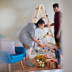 Eine Familie mit kleinem Kind dekoriert eine Stehleiter mit Lichterkette und Christbaumkugeln zum Weihnachtsbaum.