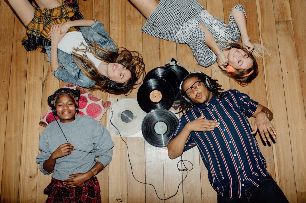vier junge Menschen liegen auf dem Boden und hören Musik über Kopfhörer