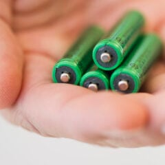 In einer Hand liegen vier grüne Batterien.