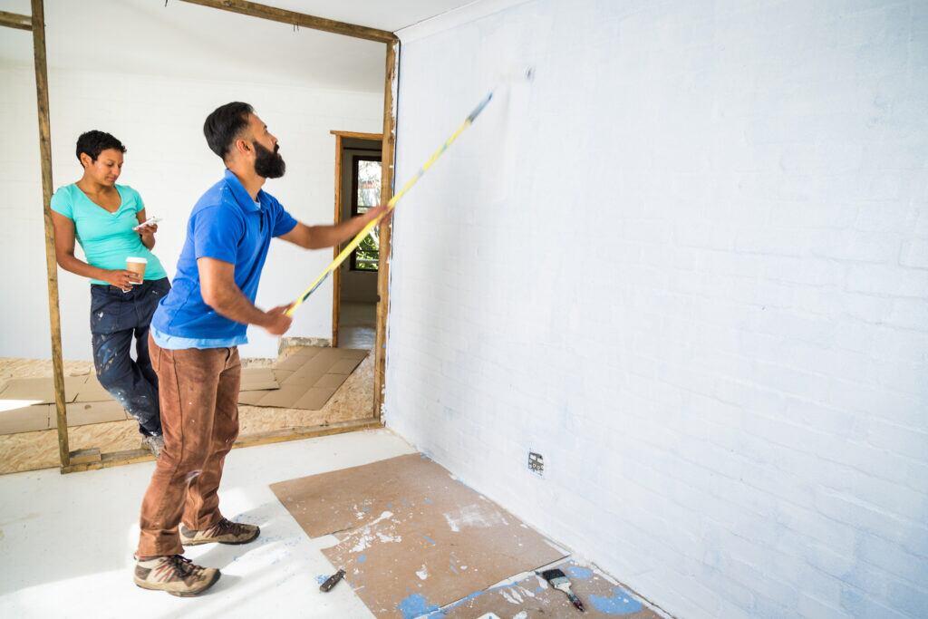 Ein Mann streicht eine Wand weiß. Im Hintergrund lehnt eine Frau an einem Balken