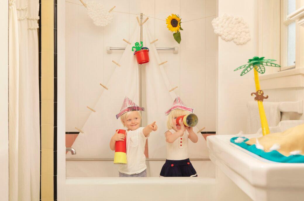 Zwei Kinder sitzen in einer Badewanne und spielen Bootfahren.