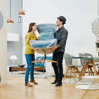 Ein Paar transportiert einen verpackten Stuhl – ob das nachhaltig ist?