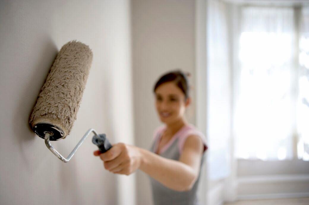 Schönheitsreparaturen: Frau beim Streichen der Wohnung