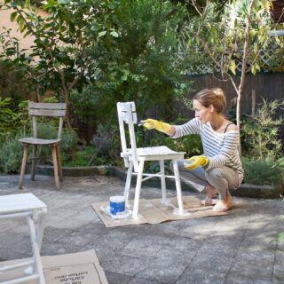Gartenmöbel: Frau streicht alte Gartenstühle weiß