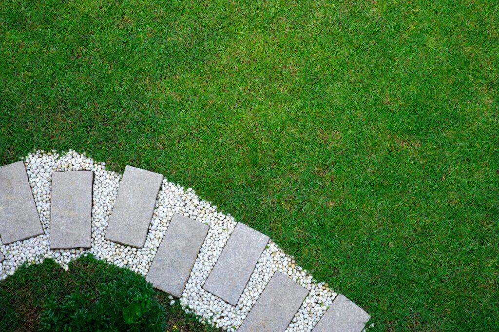 Auch größere Betonplatten können ansprechend als Gartenweg angelegt werden – hier im Kiesbett