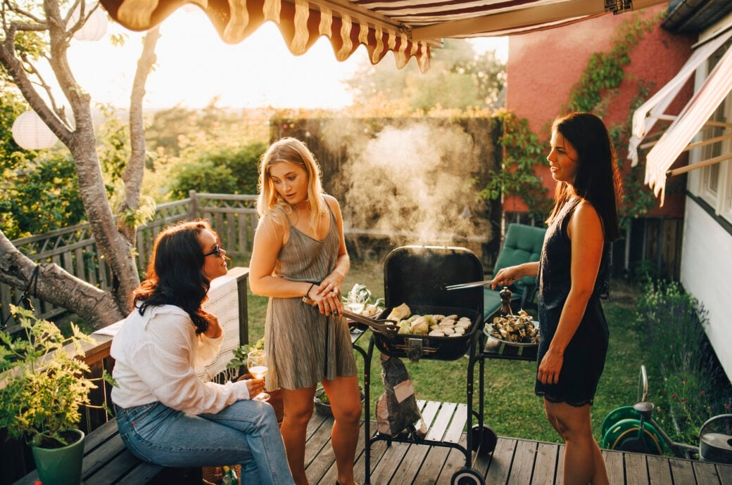 3 Frauen stehen um einen Grill