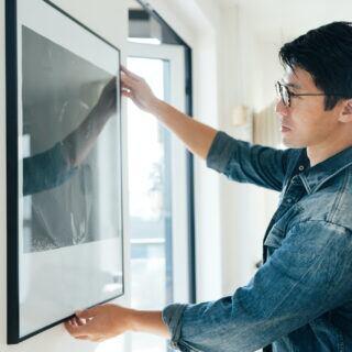 Ein Mann hängt ein Bild an eine Wand