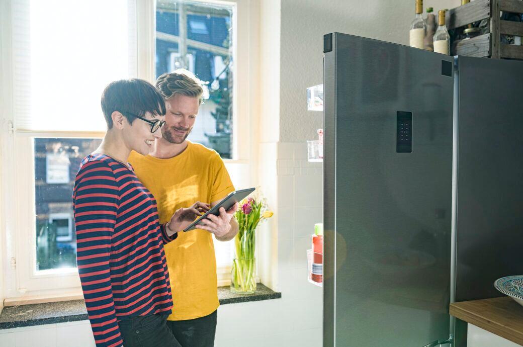 Ein Pärchen steht vor einem modernen Kühlschrank