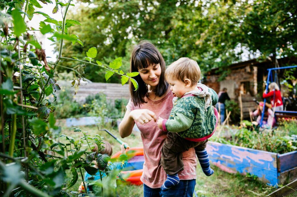 Mutter mit Kind im Schrebergarten