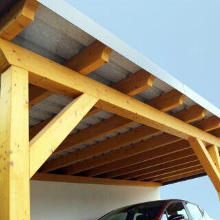 Ein Auto steht unter einem Carport aus Holz.