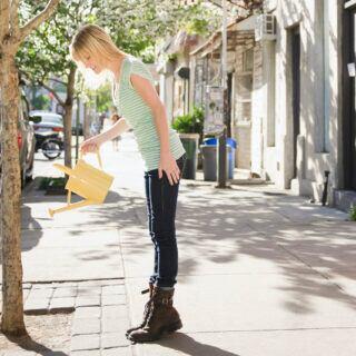 Eine Frau gießt einen Baum in der Stadt am Straßenrand