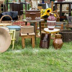 Auf einem Rasenstück stehen an einem Flohmarktstand viele unterschiedliche Töpfe, Vasen und Gefäße.