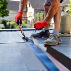 Ein Handwerker auf einem Flachdach
