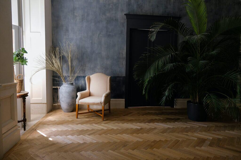 Riesige Palme im Wohnzimmer mit Sessel und Schrank