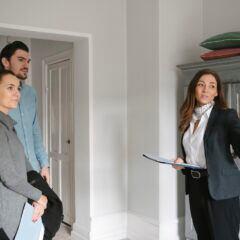 Wohnungsbesichtung mit Maklerin und einem jungen Paar