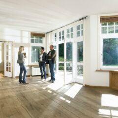 Ein Paar schaut sich mit dem Vermieter eine leere Wohnung an