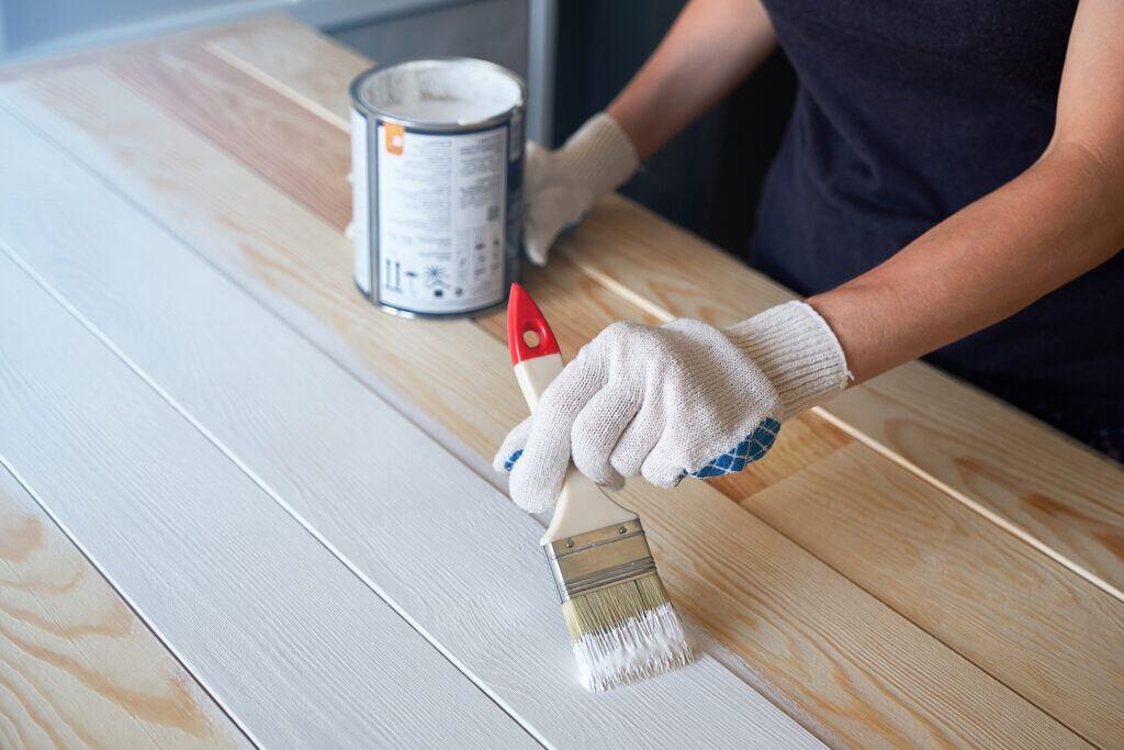 Eine Person streicht mit weißer Farbe ein Holzbrett