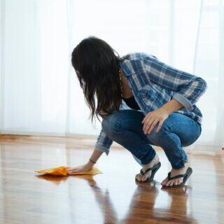 Eine Frau wischt den Holzboden