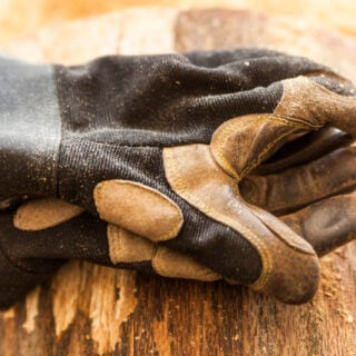 Arbeitshandschuhe liegen auf einem Holzstück