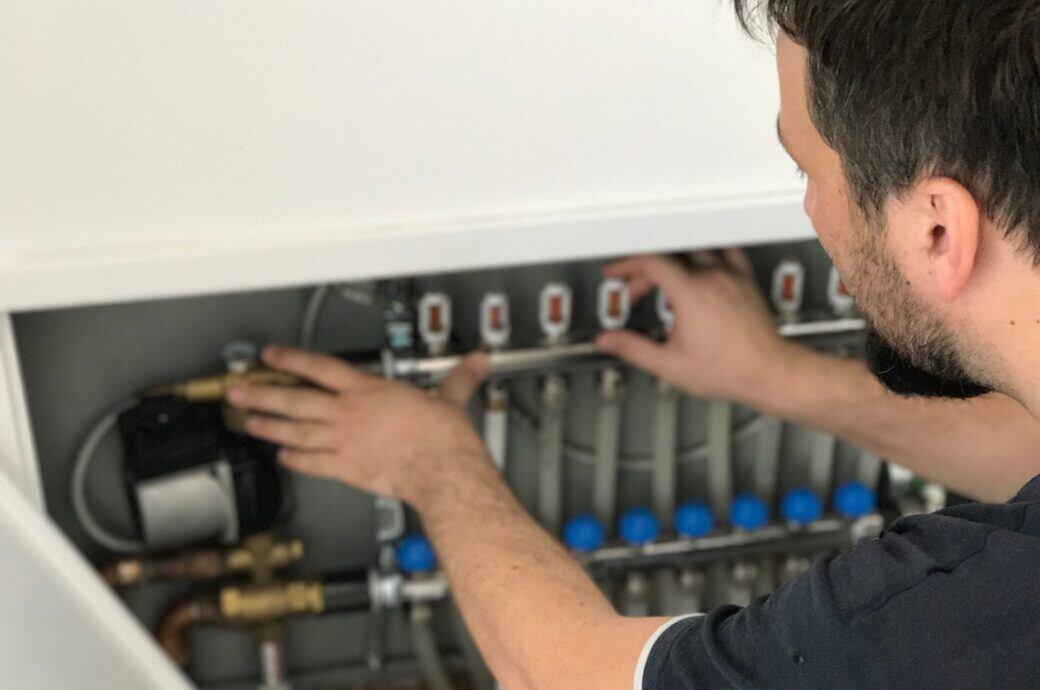 Ein Heiztechniker an einer Heizung