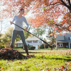 Eine Frau recht Laub im Garten