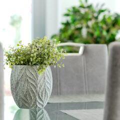 Künstliche Zimmerpflanzen: Eine grüne künstliche Zimmerpflanze in einem grauen Blumentopf